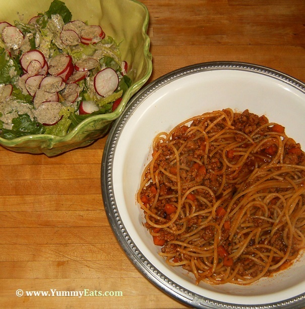 Spaghetti Bolognese and Green Salad topped with Radishes, prepared using ingredients and recipes from Blue Apron.